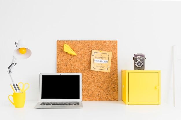 Stilvolle tabelle mit laptop und korkvorstand