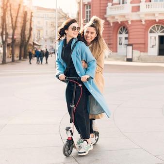 Stilvolle teenager, die einen elektroroller fahren