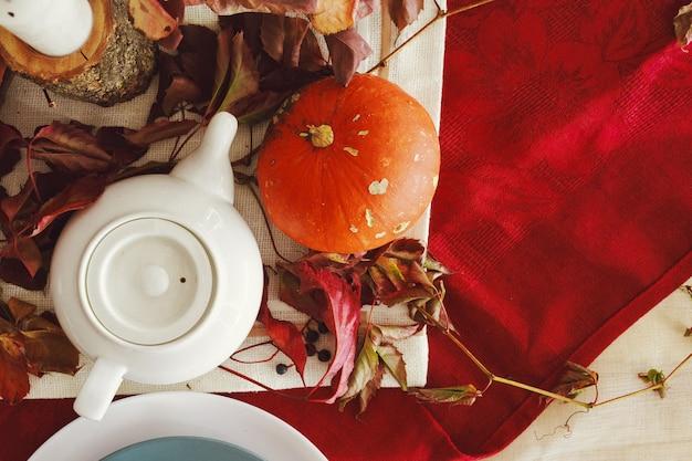 Stilvolle thanksgiving-herbsttischdekoration mit kürbis und getrockneten zweigen