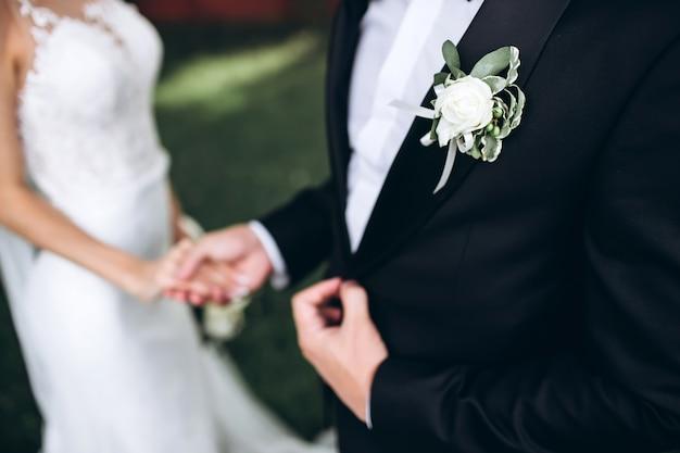 Stilvolle trauzeugen, die dem glücklichen bräutigam helfen, sich am morgen für die hochzeitszeremonie fertig zu machen. luxusmann im anzug im zimmer. hochzeitstag. Premium Fotos
