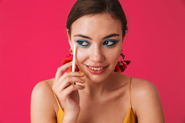 Stilvolle trendige frau, die ohrringe trägt, die beiseite schauen und weißen stift für make-up halten