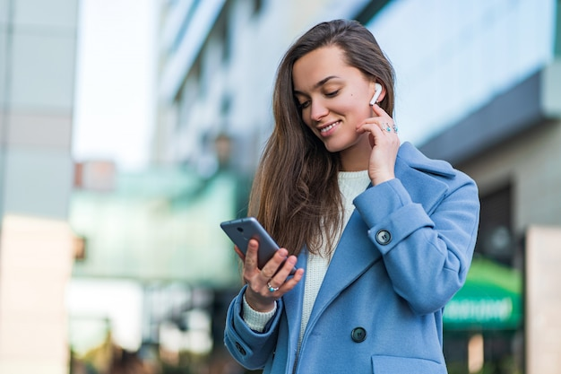 Stilvolle trendige glückliche freudige brünette frau in einem blauen mantel hält ein smartphone und verwendet drahtlose weiße kopfhörer, um musik im stadtzentrum zu hören. moderne menschen