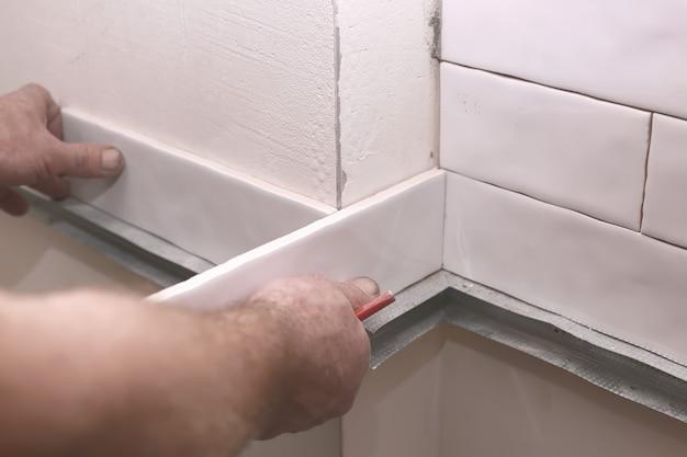 Stilvolle trendige weiße keramikfliesen an der küchenwand. hände beim verlegen von weißen rechteckigen fliesen an der badezimmerwand. renovierung von wohnungen und bädern.