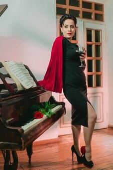 Stilvolle und elegante frau mit kreativem rotem mantel, der mit roter rose auf dem klavier steht und sich lehnt