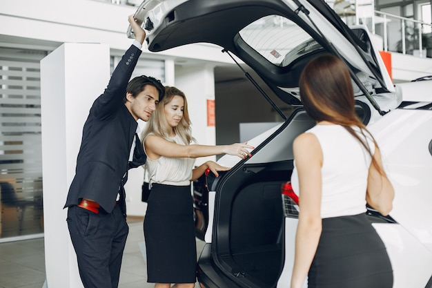 Stilvolle und elegante leute in einem autosalon