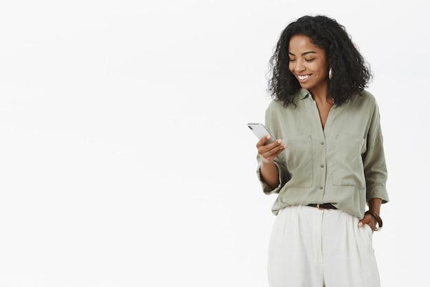 Stilvolle und erfolgreiche dunkelhäutige afrikanische unternehmerin, die das lächelnde smartphone überprüft