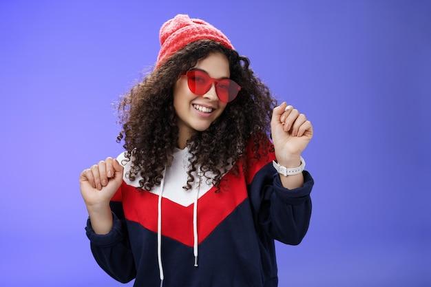 Stilvolle und feminine freundin tanzen, die spaß haben, sich optimistisch zu fühlen, wie das wetter sich warm und gemütlich in einer stilvollen roten mütze und einer sonnenbrille anfühlt, die mit erhobenen händen und breitem lächeln über blauer wand tanzt.