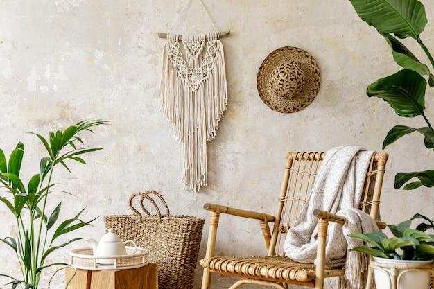 Stilvolle und florale komposition des wohnzimmerinterieurs mit rattansessel, vielen tropischen pflanzen in designtöpfen, dekoration, makramee und eleganten persönlichen accessoires in gemütlicher wohnkultur.