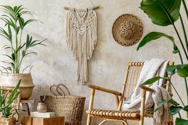 Stilvolle und florale komposition des wohnzimmers mit rattansessel, vielen tropischen pflanzen in designtöpfen, dekoration, makramee und eleganten persönlichen accessoires in gemütlicher wohnkultur.