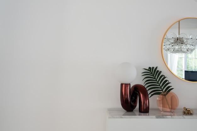 Stilvolle vertikale zusammensetzung der roten spiegel-tischlampe mit gold stationär auf weißer marmorplatte mit kopierraum auf weißer wand