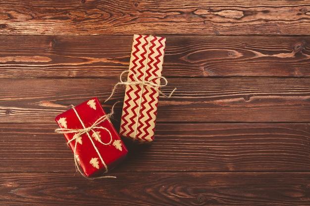 Stilvolle verzierte weihnachtsgeschenke über braunem hölzernem hintergrund
