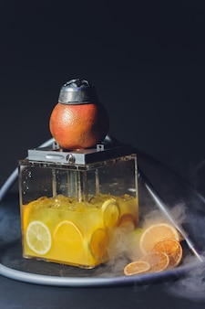 Stilvolle wasserpfeife mit dem aroma grapefruit zum entspannen. grapefruit shisha. shisha lounge.