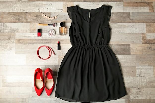Stilvolle weibliche kleidung mit accessoires auf holzuntergrund