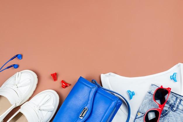 Stilvolle weibliche sommerkleidung und accessoires in den farben rot, blau und weiß, kopierraum.
