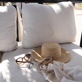 Stilvolle weibliche sonnenbrille, strohhut, einkaufstasche auf weißer lounge-couch mit kissen.