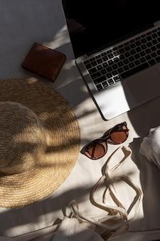 Stilvolle weibliche sonnenbrille, strohhut, einkaufstasche, laptop, brieftasche auf weißer lounge-couch mit kissen
