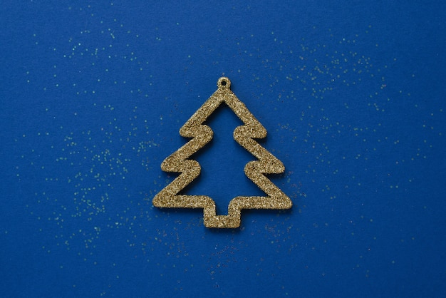 Stilvolle weihnachts- oder neujahrsgrußkarte. weihnachtsspielzeug goldener weihnachtsbaum auf einem blauen hintergrund mit pailletten