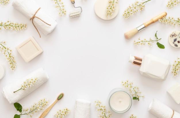 Stilvolle weiße spa-komposition. blühende zweige der vogelkirsche auf weißem hintergrund. weiße kerze, seife, sahne, handtücher. speicherplatz kopieren. flach liegen.