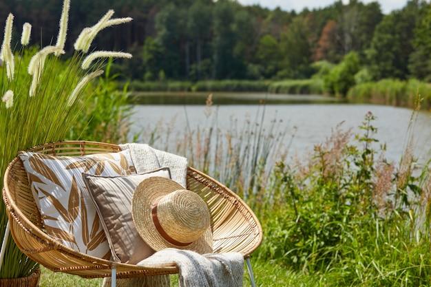 Stilvolle zusammensetzung des gartens im freien auf dem see mit design rattan sessel couchtisch plaid kissen getränke und elegante accessoires
