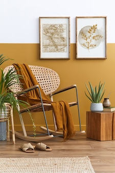Stilvolle zusammensetzung des wohnzimmer interieurs mit design rattan sessel, zwei poster rahmen, pflanzen, würfel, palid und persönliche accessoires in honiggelber wohnkultur