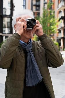 Stilvoller älterer mann in der stadt, der mit der kamera fotos macht