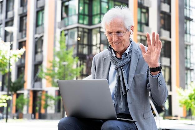 Stilvoller älterer mann in der stadt mit laptop für videoanrufe
