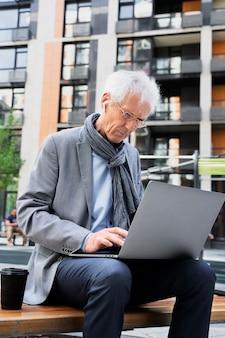 Stilvoller älterer mann in der stadt mit laptop