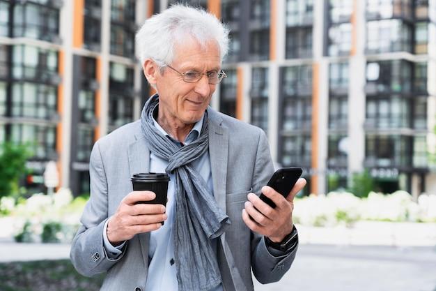 Stilvoller älterer mann in der stadt mit smartphone beim kaffeetrinken