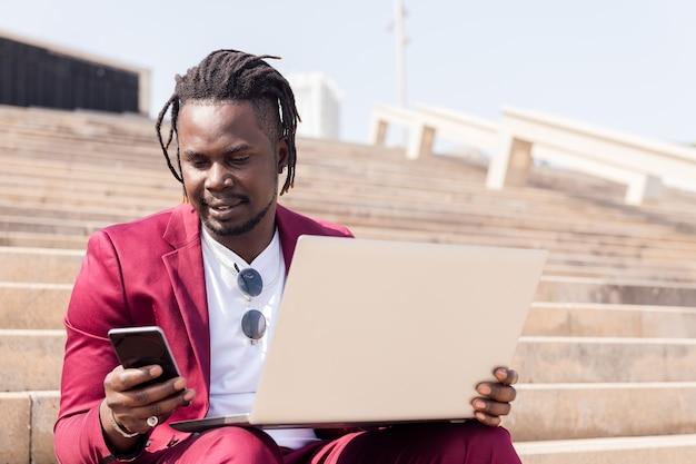 Stilvoller afrikanischer geschäftsmann, der im freien mit laptop und smartphone arbeitet
