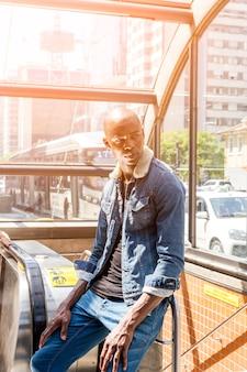 Stilvoller afrikanischer junger mann, der am eingang der u-bahn in der stadt sitzt