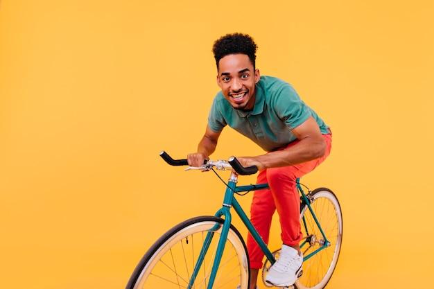 Stilvoller afrikanischer kerl im grünen t-shirt und in den weißen turnschuhen, die auf fahrrad aufwerfen. glückseliger schwarzer mann, der auf fahrrad fährt.