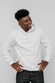 Stilvoller afroamerikanermann, der einen weißen kapuzenpulli trägt