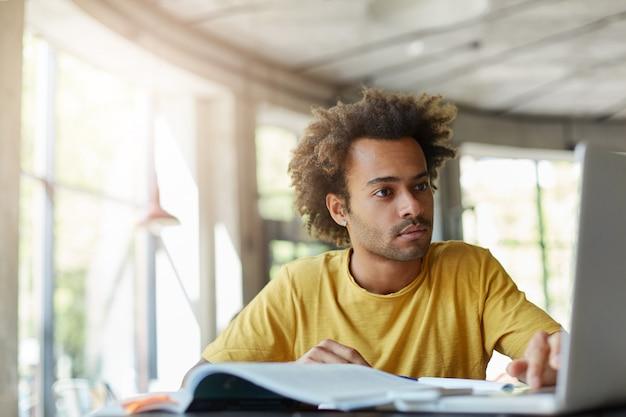 Stilvoller afroamerikanischer hipster-mann mit buschiger frisur, der lässiges t-shirt trägt, das in den bildschirm des laptops fokussiert wird, der in geräumigem hellem raum mit großen fenstern sitzt, die mit literatur und internet arbeiten