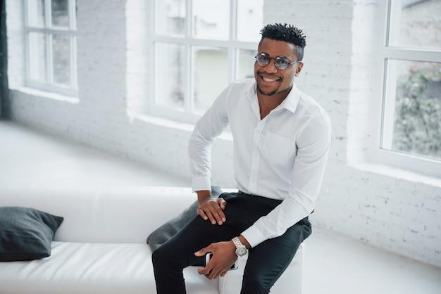 Stilvoller afroamerikanischer kerl in der büroabnutzung und in gläsern, die am rand der couch und des lächelns sitzen