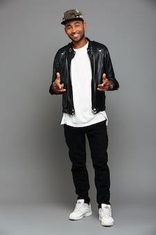 Stilvoller afroamerikanischer mann, der mit zwei fingern auf sie, schauend zeigt