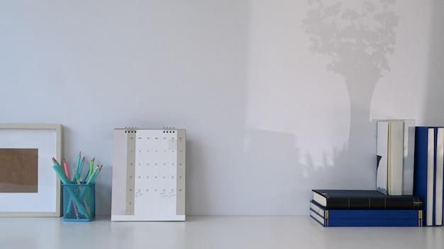 Stilvoller arbeitsbereich mit kalender, büchern, schreibwaren und kopienraum auf weißem tisch.