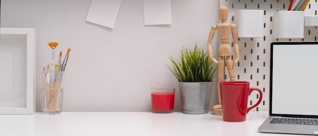 Stilvoller arbeitsbereich mit kopierbereich, modell-laptop, becher, malpinseln und dekorationen