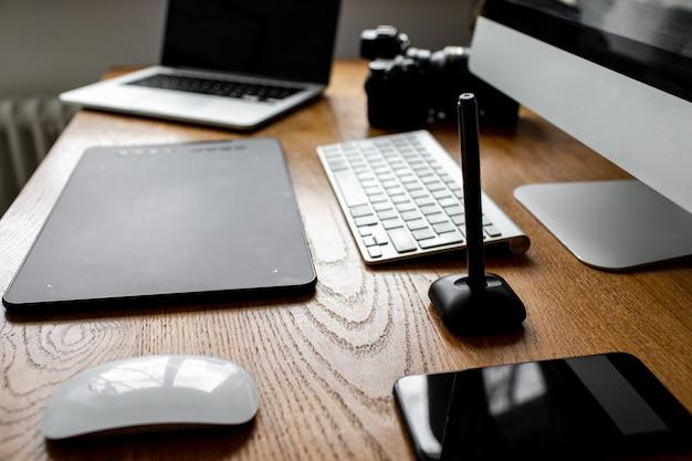 Stilvoller arbeitsbereich mit laptop zu hause oder im studio. arbeitsplatz des fotografen