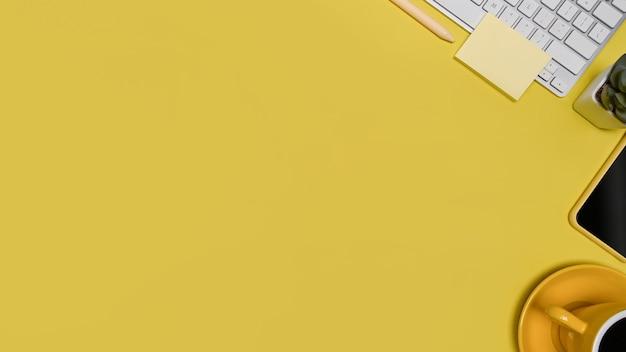Stilvoller arbeitsbereich von oben mit haftnotiz, smartphone und kaffeetasse auf gelbem hintergrund.