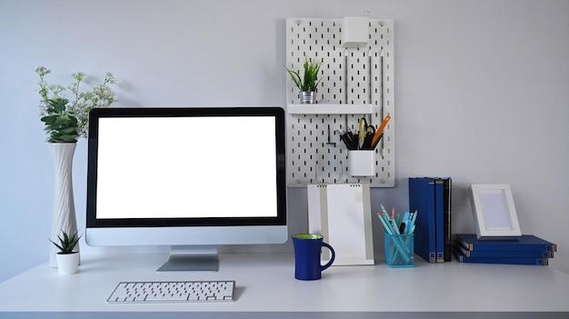 Stilvoller arbeitsplatz mit computer- und bürobedarf auf weißem tisch.