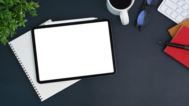 Stilvoller arbeitsplatz mit digitalem tisch, kaffeetasse, zimmerpflanze und notizbuch auf schwarzem leder.