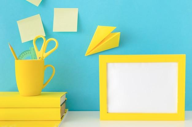 Stilvoller arbeitsplatz mit gelbem fotorahmen und papierfläche