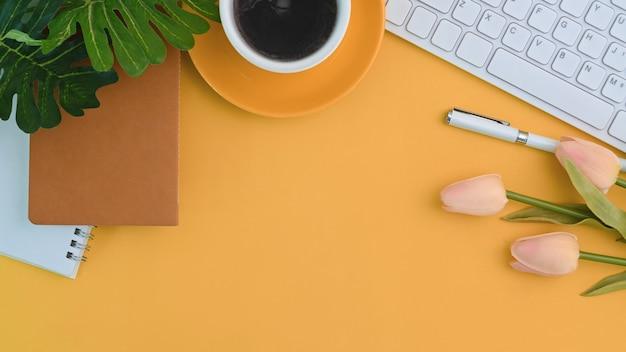 Stilvoller arbeitsplatz mit kaffeetasse, blumen, notizbuch und tastatur auf gelbem hintergrund.