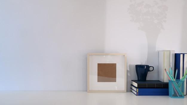 Stilvoller arbeitsplatz mit kaffeetasse, büchern, bleistifthaltern und kopienraum auf weißem tisch.