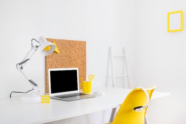 Stilvoller arbeitsplatz mit korkbrett und gelbem stuhl