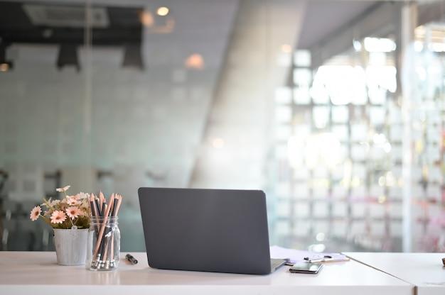 Stilvoller arbeitsplatz mit laptop-computer, büroartikel, blume im büro. schreibtisch arbeitskonzept.