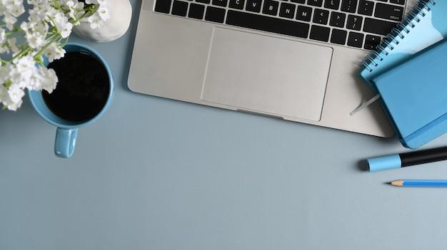 Stilvoller arbeitsplatz mit laptop-computer, kaffeetasse, briefpapier und notizbuch auf blauem pastelltisch.