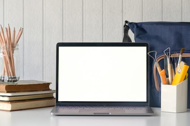 Stilvoller arbeitsplatz mit modelllaptop auf schreibtischtabelle.