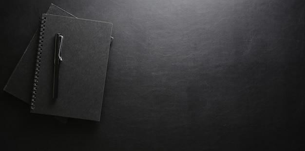 Stilvoller arbeitsplatz mit notizbuch und stift auf schwarzem ledernem schreibtisch