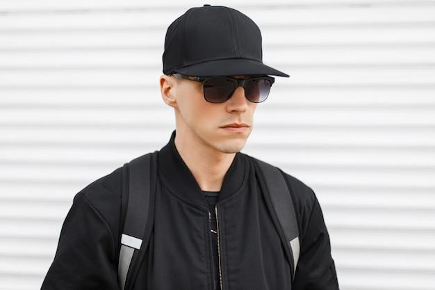 Stilvoller attraktiver hipster-mann in einer schwarzen basketballkappe in einer modischen schwarzen sonnenbrille in einer trendigen jacke mit einem schwarzen rucksack auf seinen schultern nahe der weißen metallwand. amerikaner.